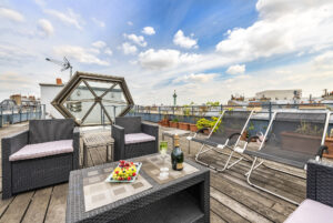 Champagne flutes, a bottle of champagne and a fruit plate sit on a table on the rooftop of a penthouse apartment in the Marais neighborhood in Paris.