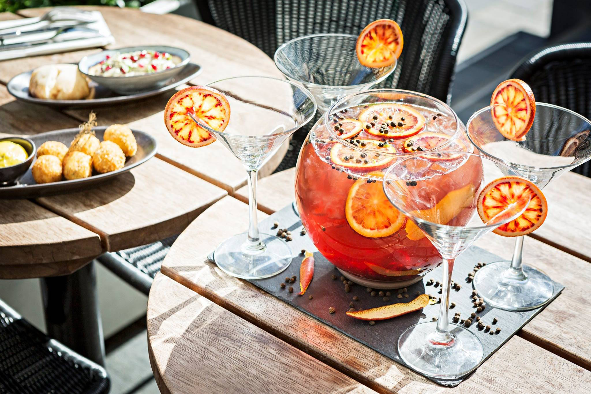 An outdoor table at Publicis Drugstore on the Champs Elysées. On top of the table are various plates of food, martini glasses with sliced fruit on the rim, and a pitcher of a bright orange beverage.