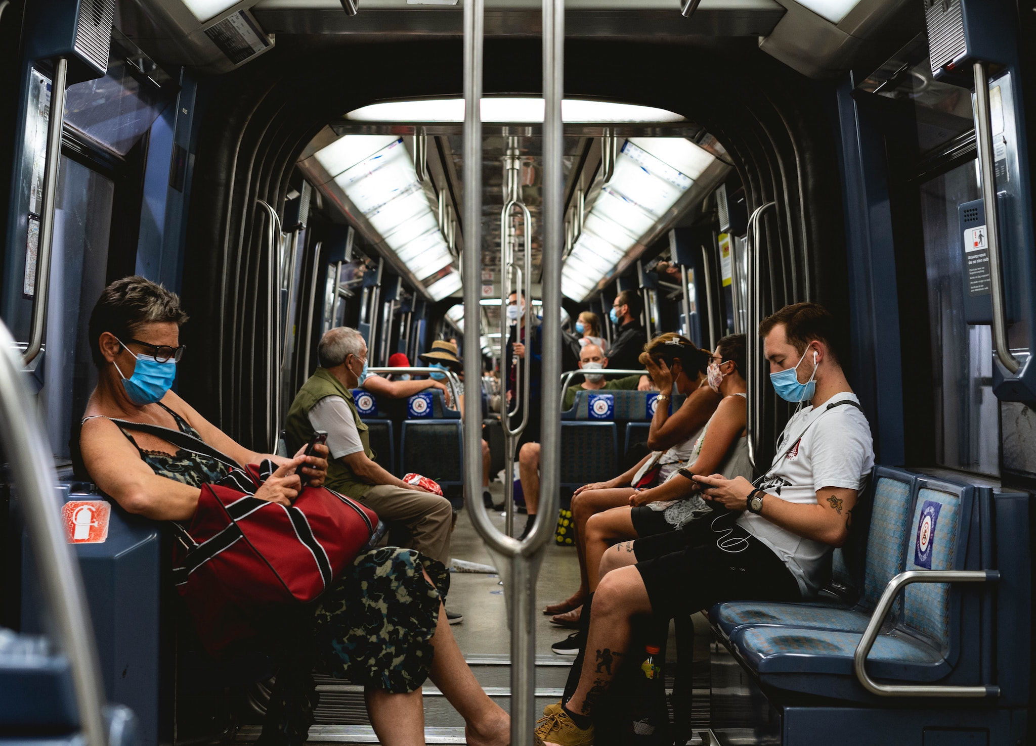 People sit in the Paris metro while wearing required face masks.