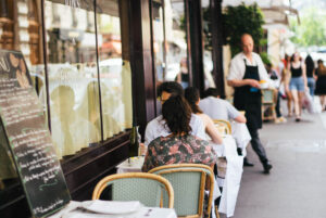 A man and a woman, seated at an outdoor table, dine at a bistro in Paris while a waiter serves a table in the background