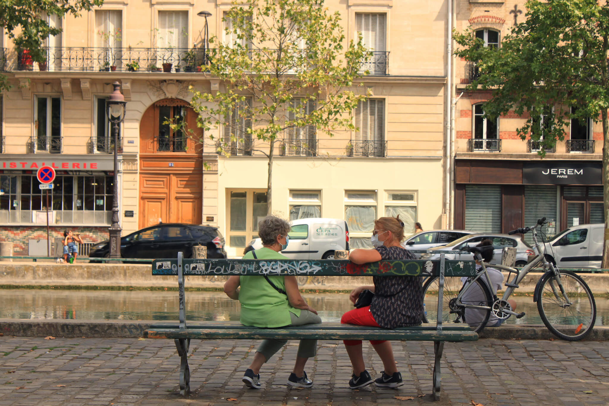 Two women sit on a bench by Paris's Canal St. Martin and speak to each other while wearing face masks.