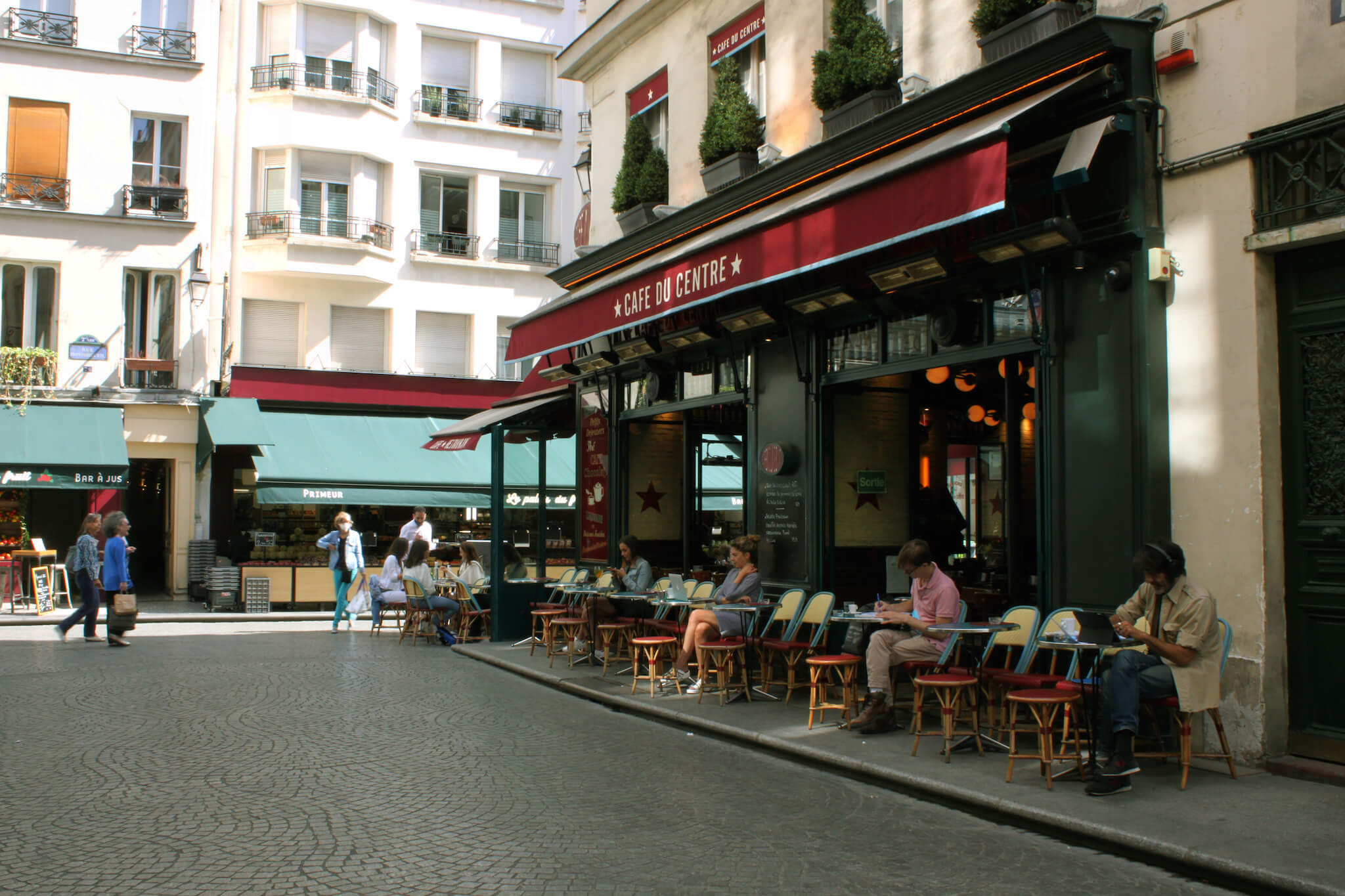 People sit socially distanced from each other at outdoor tables at a café near Rue de Montorgueil in the center of Paris.