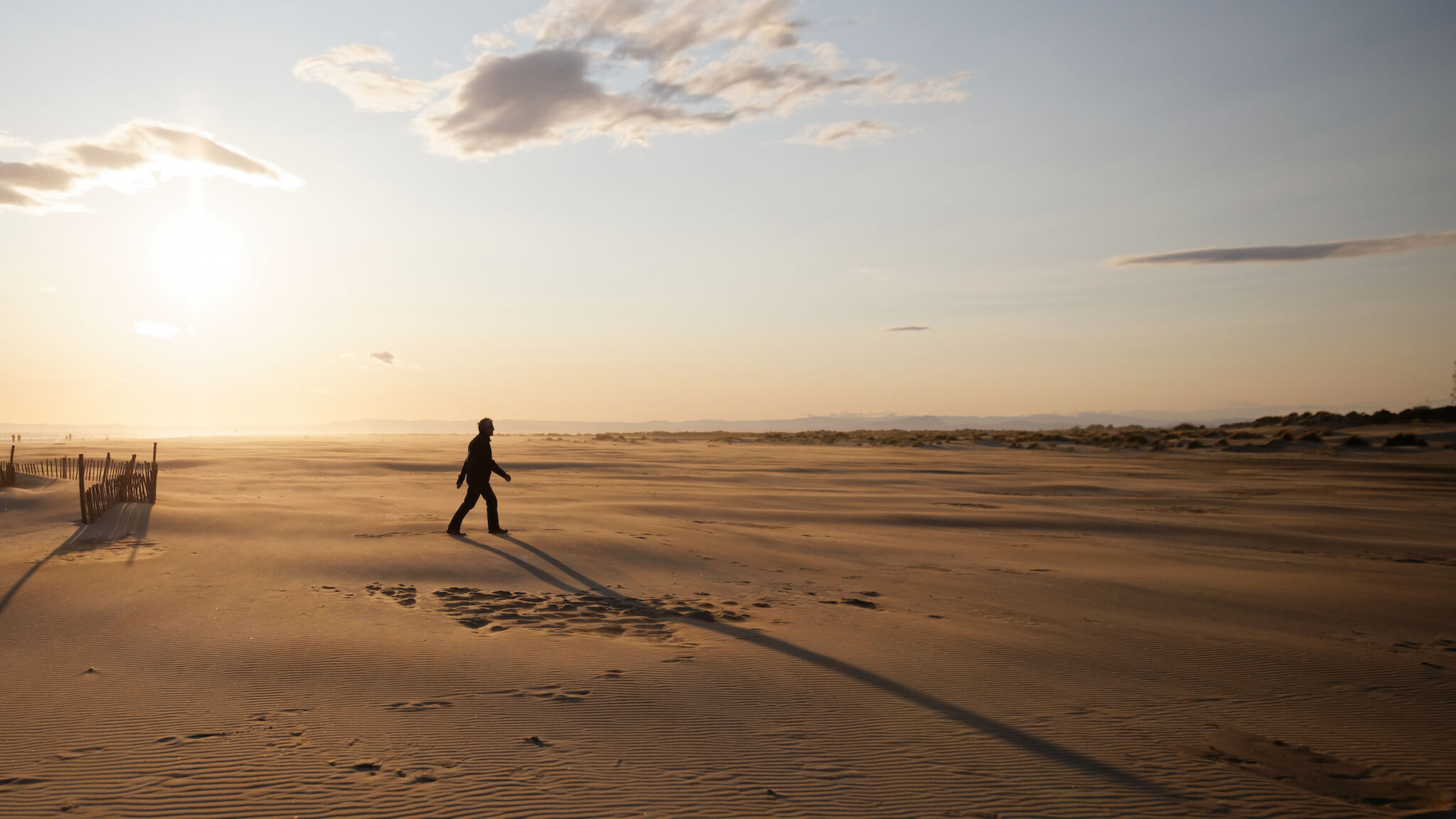 A person walks on the sandy beach of the Camargue at sunset, casting a shadow on the ground.