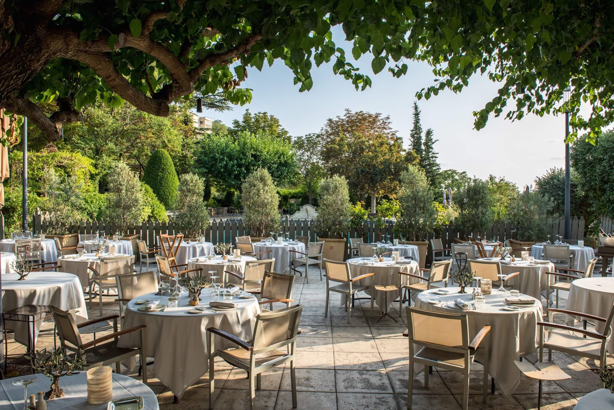 Tables and chairs are set out on a wide, sunny porch under leafy green trees at Baumanière in Arles.