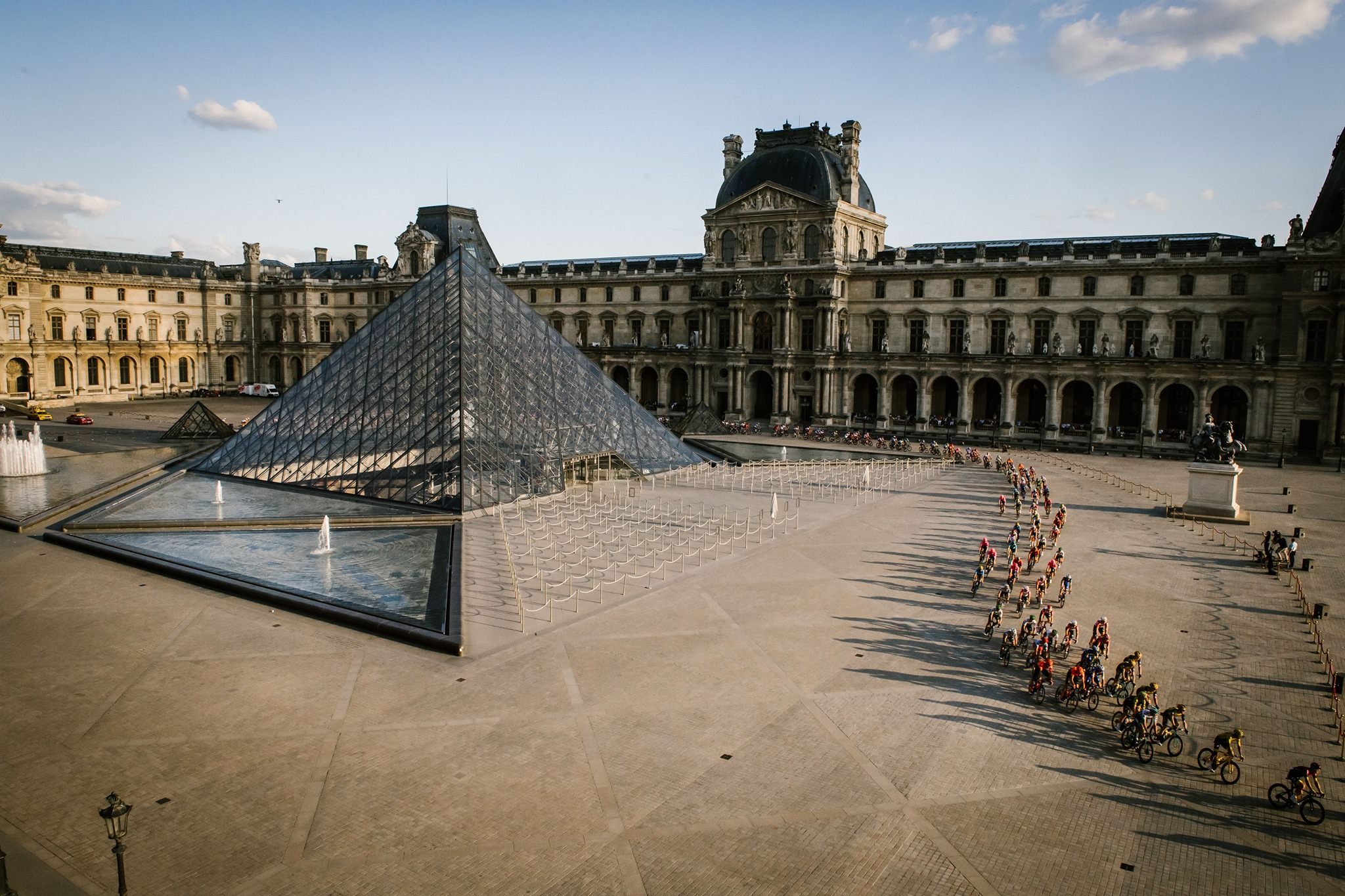 The courtyard of the Louvre, including the glass pyramid and a line of cyclists snaking through the space.
