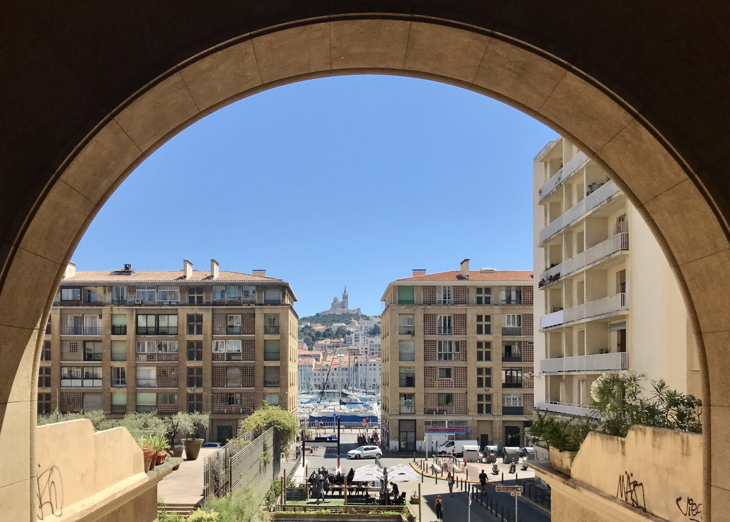 A photo through a passage way of the Vieux-Port in Marseille, peering onto apartment buildings overlooking the sea with a hilltop church in the distance.