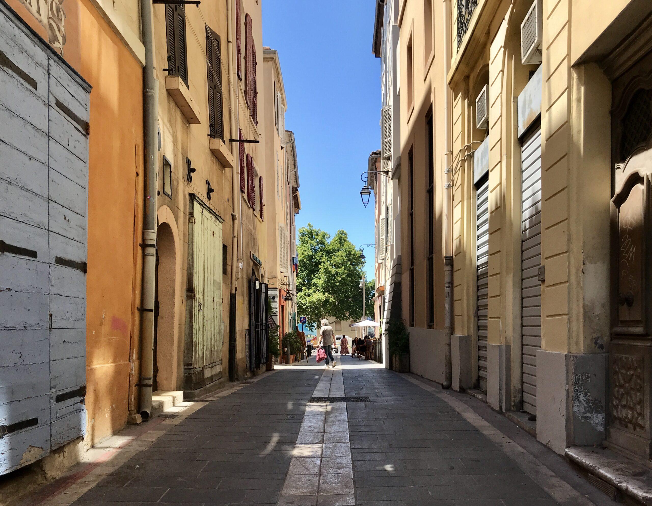 A narrow passageway between Mediteranean, sun kissed buildings in Marseille.