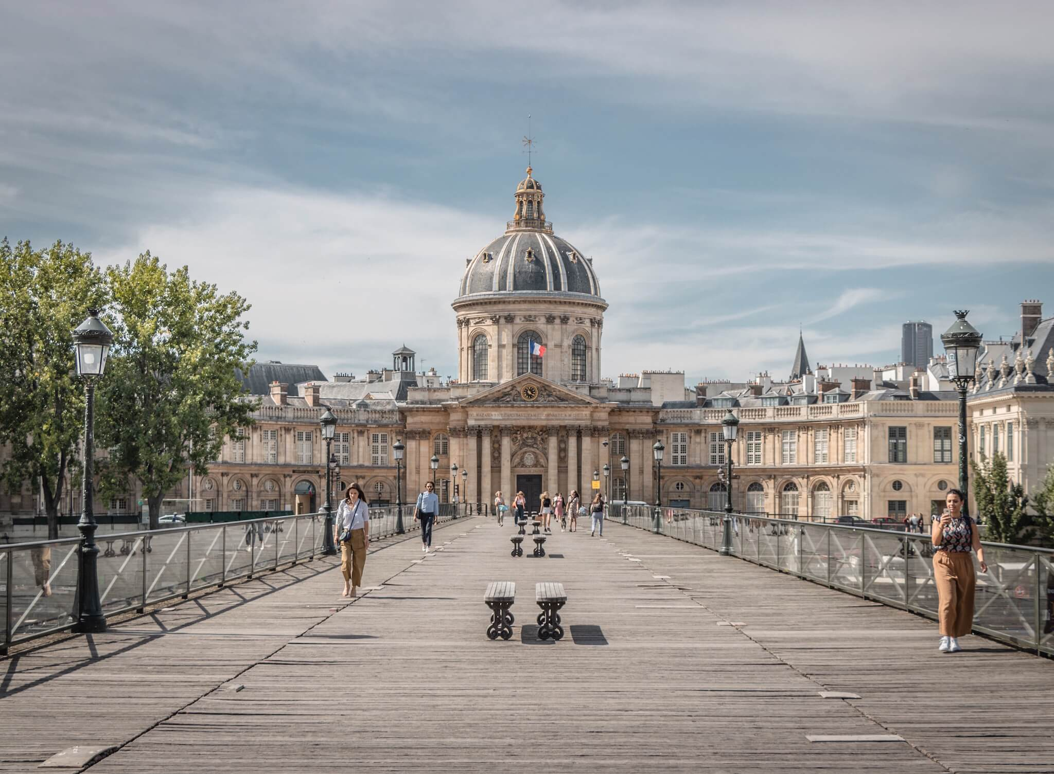 A view of the Institut de France from the Pont des Arts bridge in Paris, where people are seen walking on either side of the bridge.