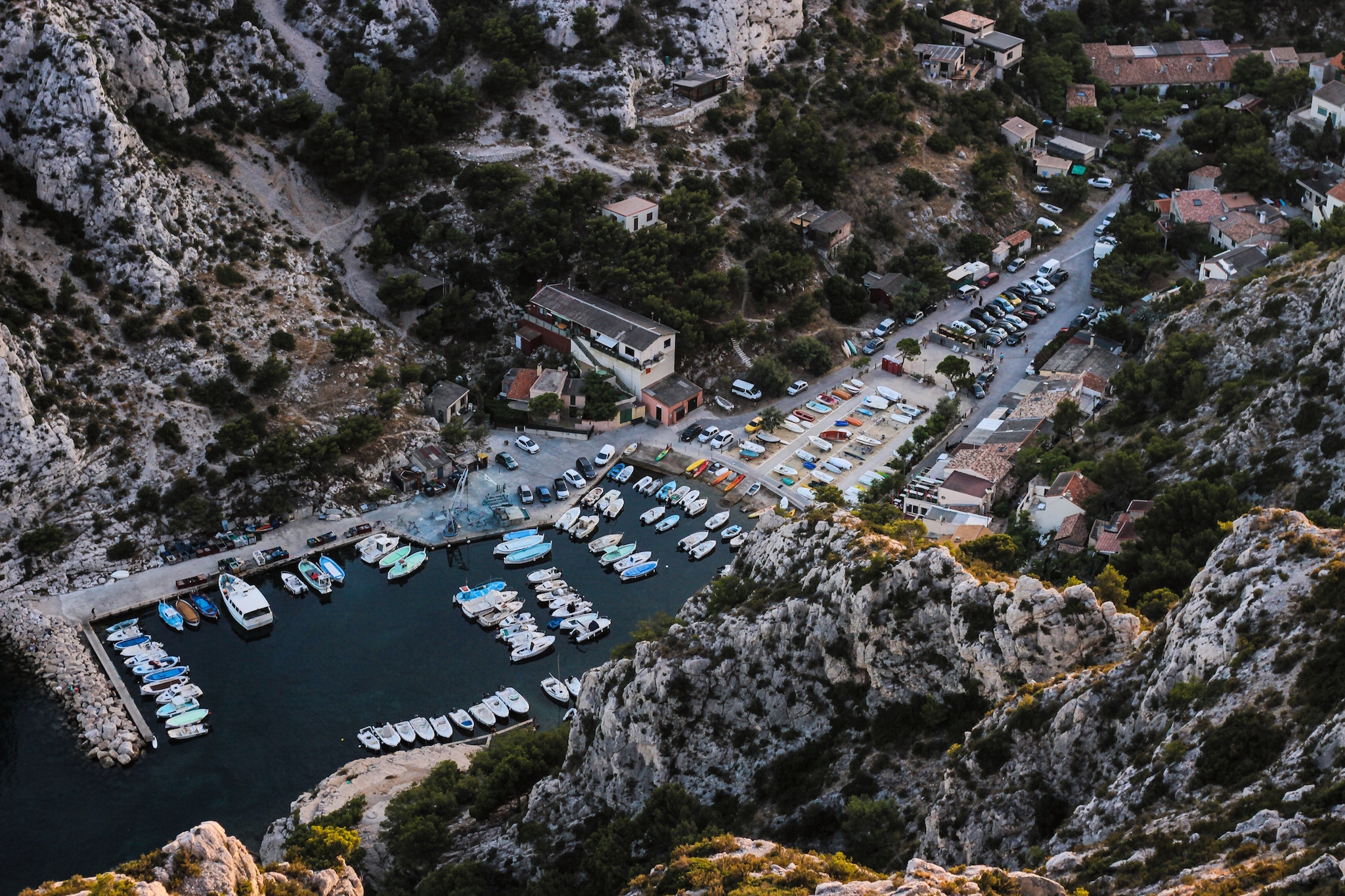A rocky bay near in the South of France, crowded with small boats and dozens of parked cars next to it.