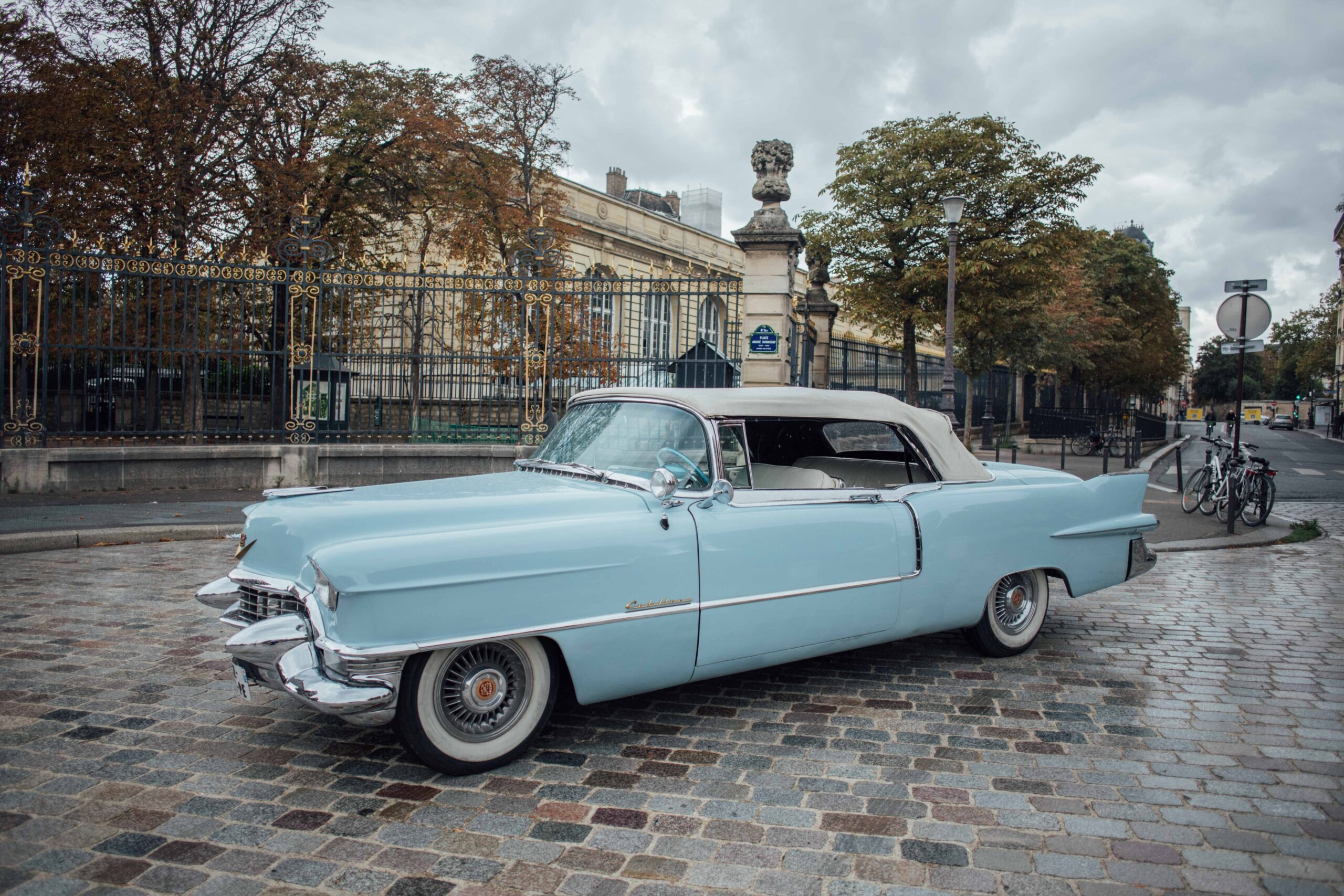 A old blue car is parked on a cobble driveway on a rainy fall day in Paris
