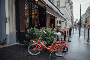 An orange bicycle parked outside a café on a rainy day in Paris