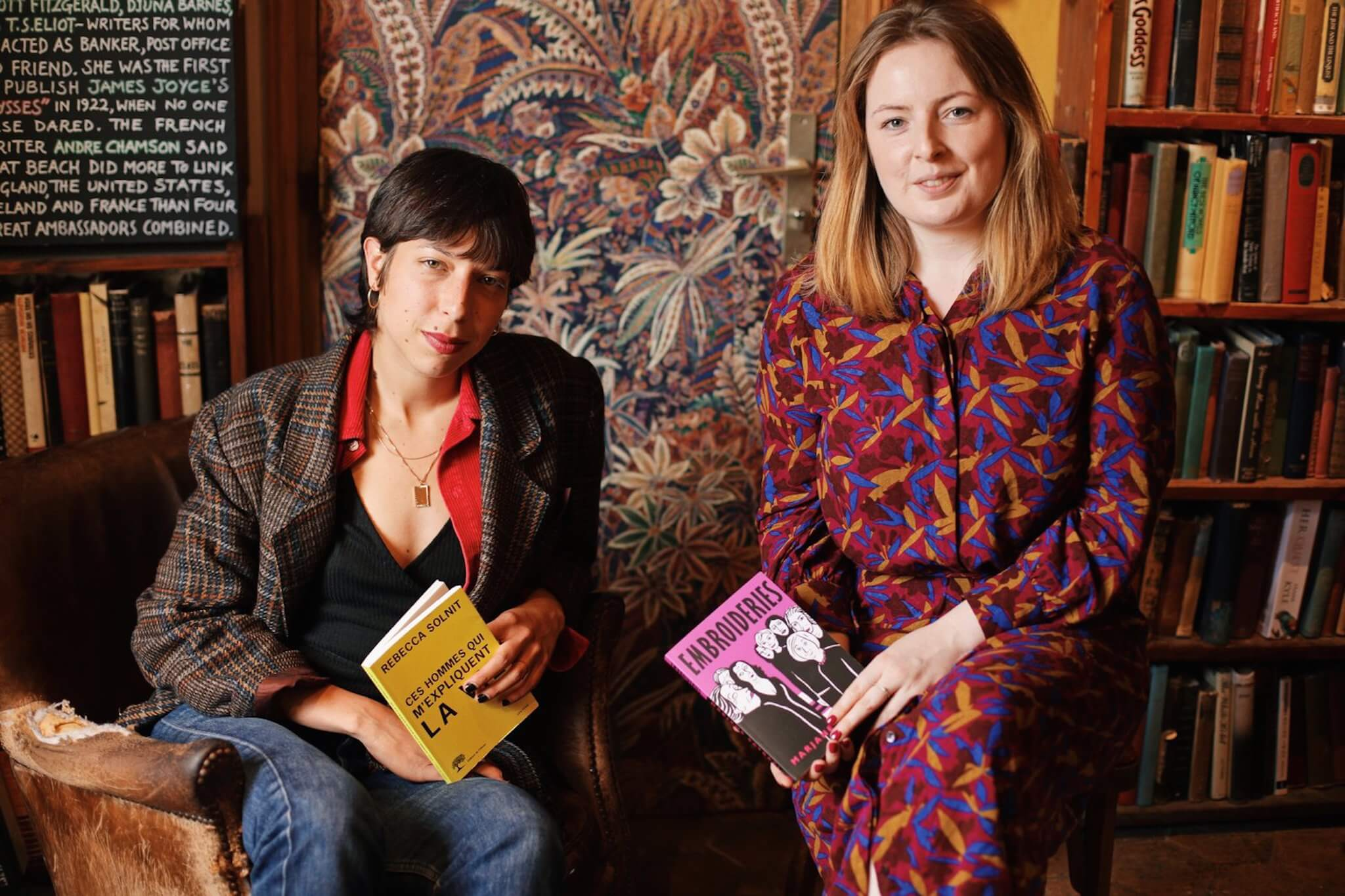 Hosts of the Feminist book club, Camille Lou to the left and Lou Binns to the right, sitting side by side with books in their hands. Camille dressed in a blazer, tshirt and jeans, Lou wearing a long, printed dress, and the two smile at the camera.