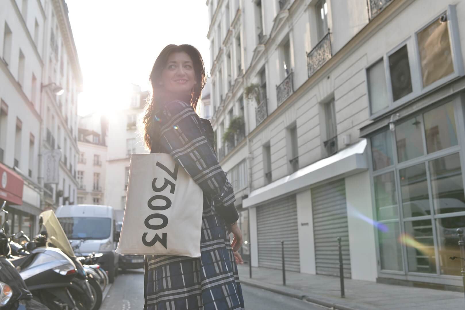 "A woman stands in the middle of a Parisian street wearing a striped patterned trench coat and holding a  white canvas tote bag that reads ""75003"" in black."